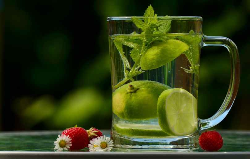 green round fruit on clear glass mug with water